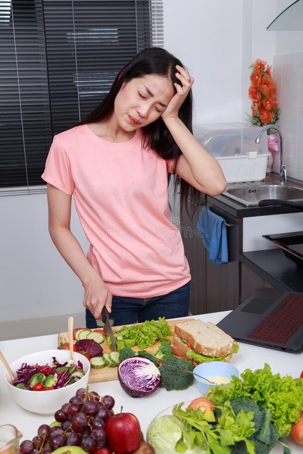 Καταθλιπτικό μαγείρεμα γυναικών στο δωμάτιο κουζινών στοκ φωτογραφίες