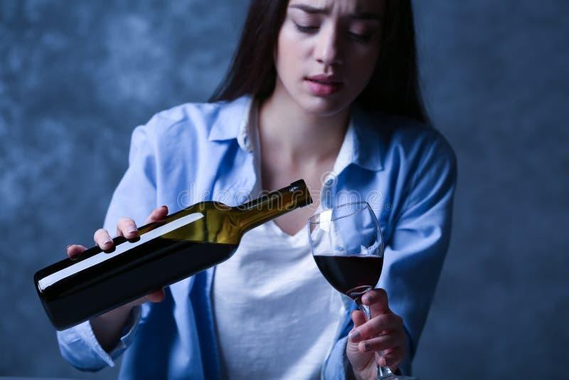 Καταθλιπτικό νέο κρασί κατανάλωσης γυναικών στο γκρίζο υπόβαθρο στοκ φωτογραφία με δικαίωμα ελεύθερης χρήσης