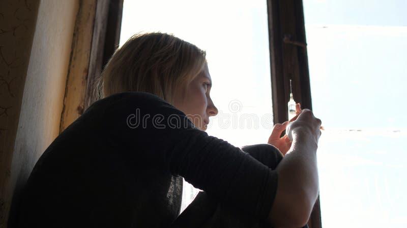 Καταθλιπτικό πρόσωπο ενός κοριτσιού που σκέφτεται για τη σύριγγα με την ηρωίνη στοκ φωτογραφία