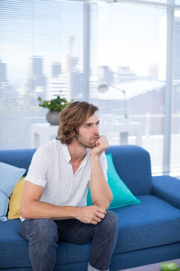 Καταθλιπτική αρσενική εκτελεστική συνεδρίαση στον καναπέ στοκ φωτογραφίες