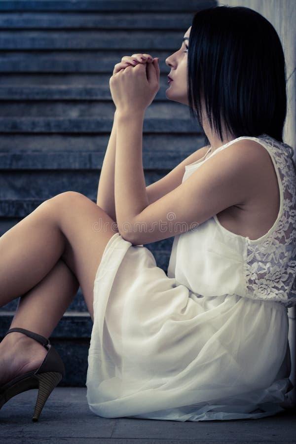 Καταθλιπτική νέα ενήλικη συνεδρίαση γυναικών στοκ εικόνες