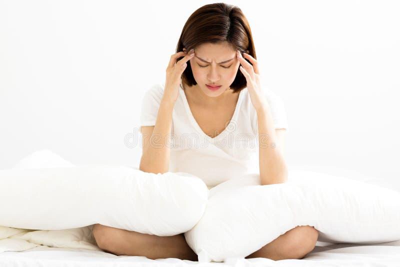Καταθλιπτική νέα συνεδρίαση γυναικών στο κρεβάτι στοκ φωτογραφία με δικαίωμα ελεύθερης χρήσης