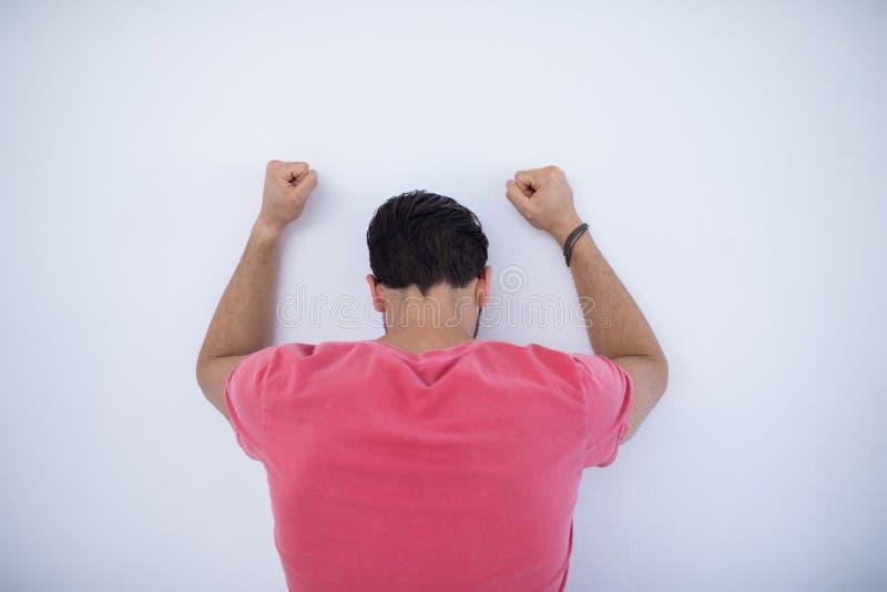 Καταθλιπτικός αρσενικός ανώτερος υπάλληλος με τα όπλα που αυξάνονται κλίση στον τοίχο στοκ εικόνες