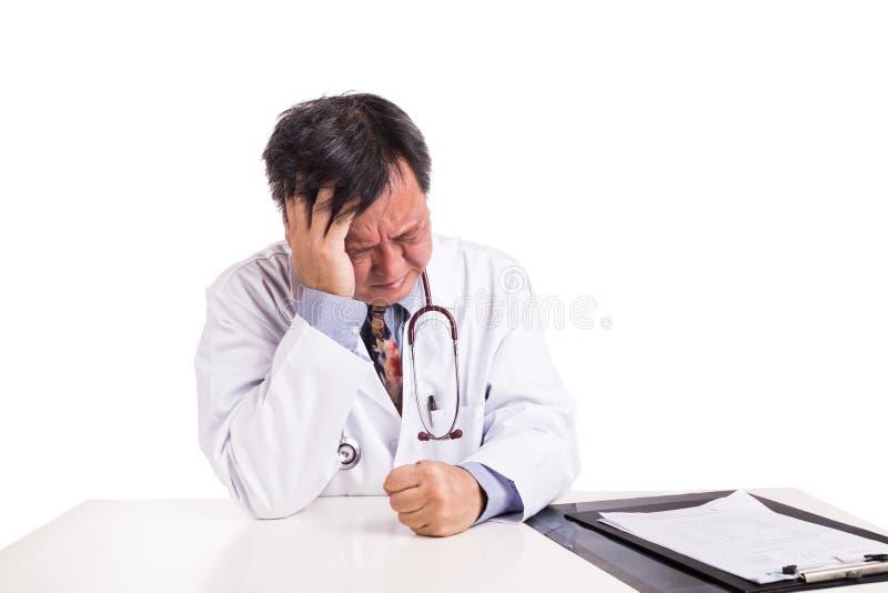 Καταθλιπτικός λυπημένος ωριμασμένος ασιατικός γιατρός που κάθεται πίσω από το γραφείο στοκ εικόνες