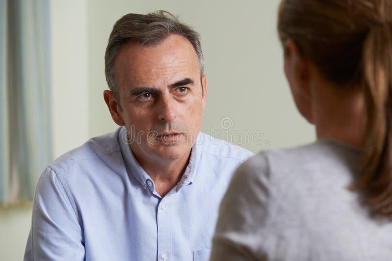 Καταθλιπτικό ώριμο άτομο που μιλά στο σύμβουλο στοκ εικόνα