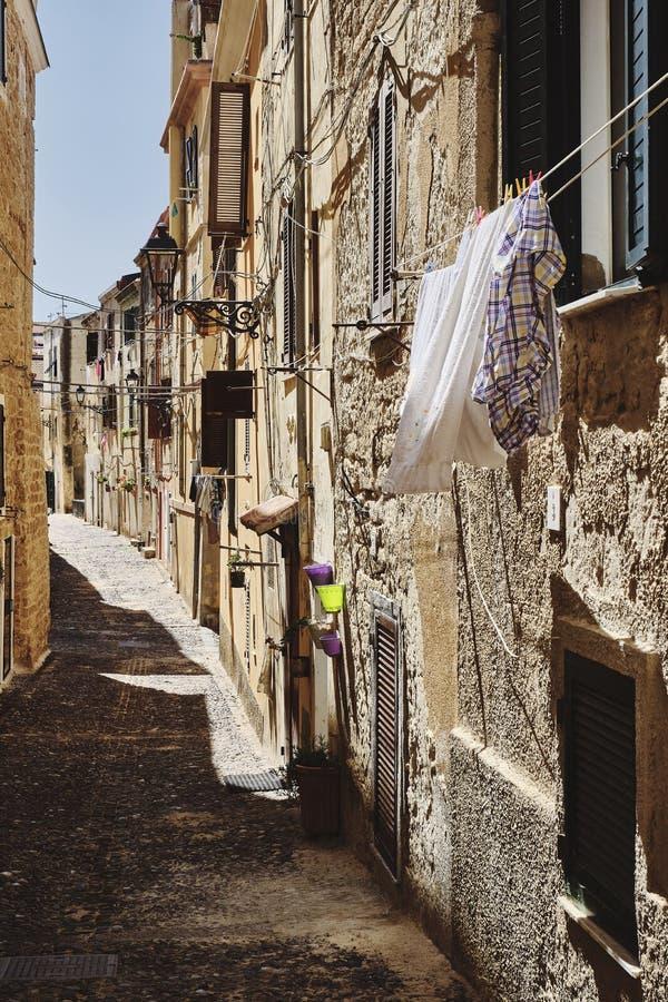 Κατακόρυφη φωτογραφία στενού δρόμου σε μια παλιά γειτονιά στην πόλη Alghero Old, στην Ιταλία στοκ εικόνες
