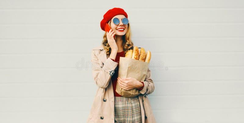 Κατακόρυφη όμορφη χαμογελαστή γυναίκα που καλεί στο τηλέφωνο, κρατώντας στο μπακάλικο τσάντα με μακριά λευκή μπαγκέτα ψωμιού στοκ φωτογραφία με δικαίωμα ελεύθερης χρήσης