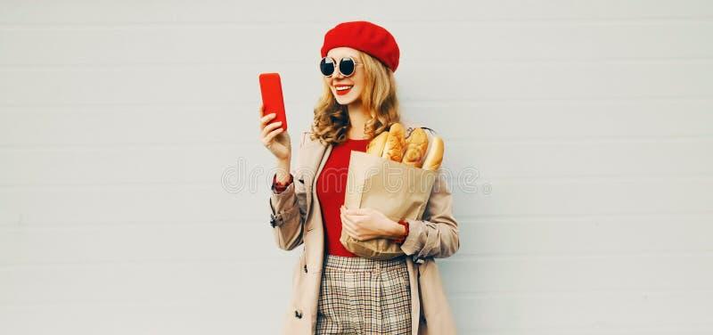Κατακόρυφη όμορφη χαμογελαστή γυναίκα που κρατά τηλέφωνο, σακούλα για ψώνια με μακρύ λευκό ψωμί με κόκκινο μπερέ στοκ εικόνες