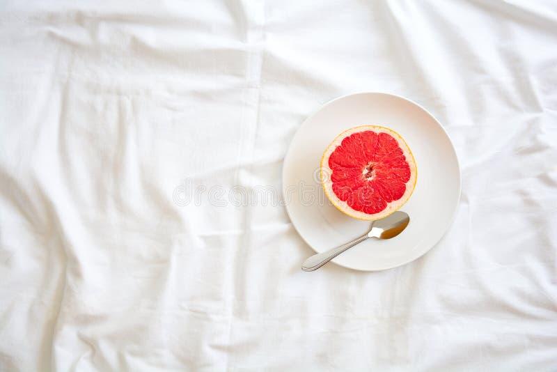 κατανάλωση έννοιας υγιής Γυναίκα που έχει το γκρέιπφρουτ στο κρεβάτι στοκ εικόνες