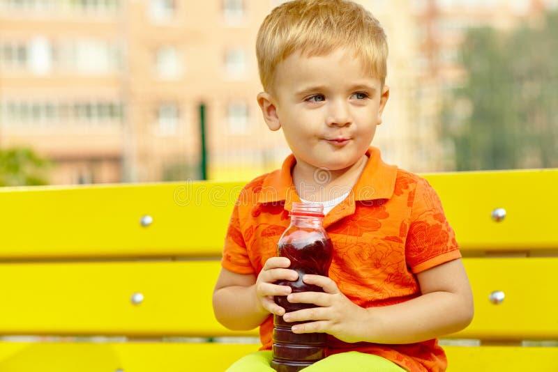 Κατανάλωση μικρών παιδιών από ένα μπουκάλι του ποτού στοκ φωτογραφίες με δικαίωμα ελεύθερης χρήσης