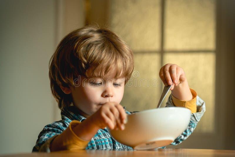 Κατανάλωση παιδιών Μικρό παιδί που έχει το πρόγευμα στην κουζίνα Χαριτωμένο παιδί που τρώει το πρόγευμα στο σπίτι E στοκ φωτογραφία