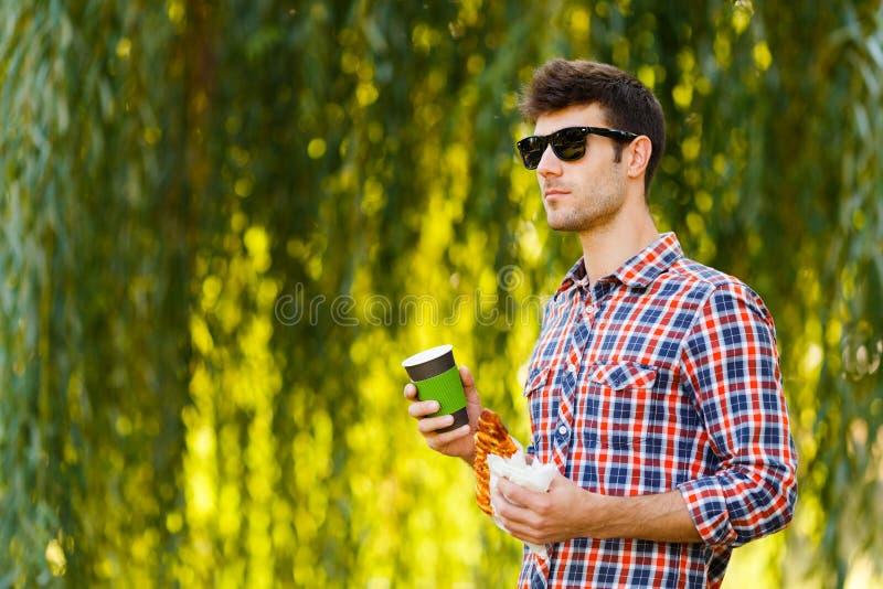 κατανάλωση της πίτσας ατόμ&o Ο εύθυμος νέος τύπος τρώει τον καφέ κατανάλωσης πιτσών στο πάρκο στοκ εικόνες