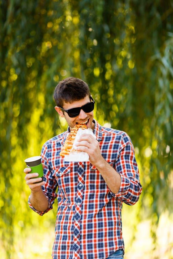 κατανάλωση της πίτσας ατόμ&o Ο εύθυμος νέος τύπος τρώει τον καφέ κατανάλωσης πιτσών στο πάρκο στοκ φωτογραφίες