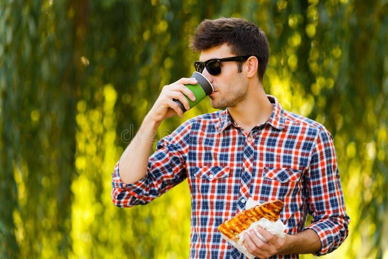 κατανάλωση της πίτσας ατόμ&o Ο εύθυμος νέος τύπος τρώει τον καφέ κατανάλωσης πιτσών στο πάρκο στοκ εικόνα με δικαίωμα ελεύθερης χρήσης