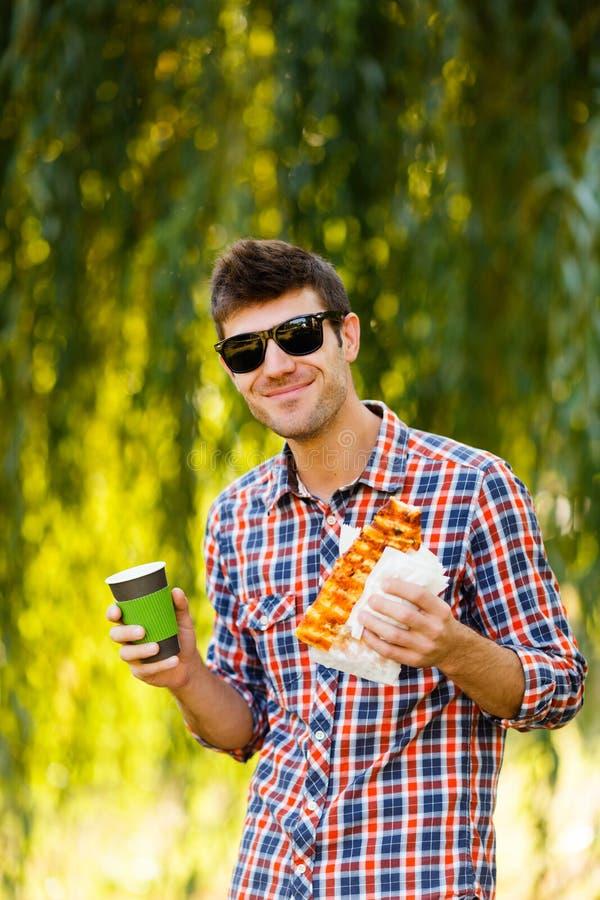 κατανάλωση της πίτσας ατόμ&o Ο εύθυμος νέος τύπος τρώει τον καφέ κατανάλωσης πιτσών στο πάρκο στοκ φωτογραφία με δικαίωμα ελεύθερης χρήσης