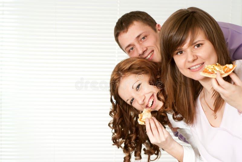 κατανάλωση της πίτσας τρία ανθρώπων στοκ φωτογραφία