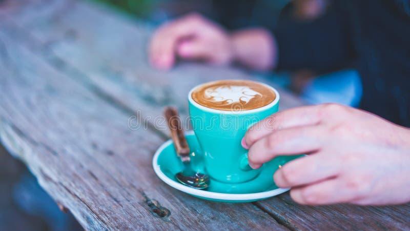 Κατανάλωση του καυτού καφέ Latte στο πράσινο φλυτζάνι στοκ εικόνες