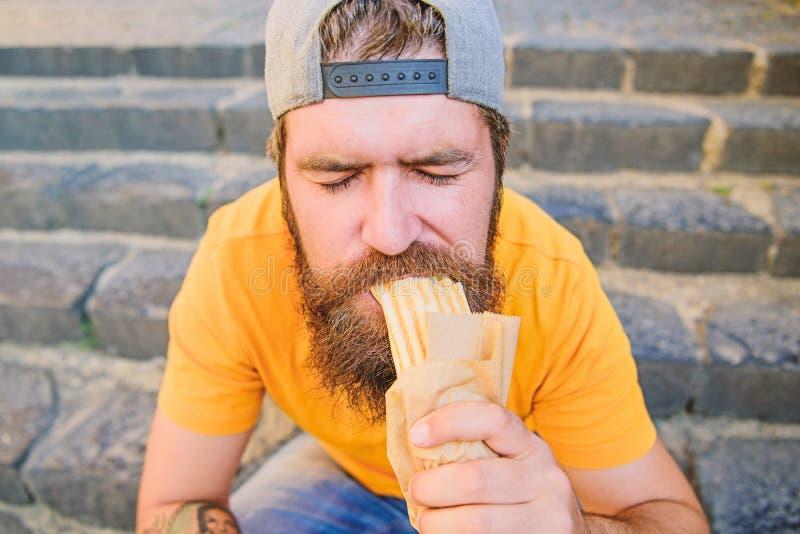 Κατανάλωση του μακρύτερου σκυλιού στην πόλη Ο πεινασμένος τύπος απολαμβάνει έξω Γενειοφόρο άτομο που τρώει το ανθυγειινό σάντουιτ στοκ φωτογραφία με δικαίωμα ελεύθερης χρήσης