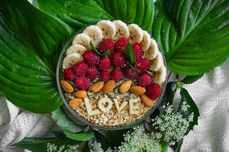 Κατανάλωση του υγιούς κύπελλου προγευμάτων Η ΑΓΑΠΗ λέξης σε ένα πιάτο με ένα υγιές γεύμα Σμέουρο, μπανάνα, καρύδια Χορτοφάγος ένν στοκ φωτογραφία με δικαίωμα ελεύθερης χρήσης