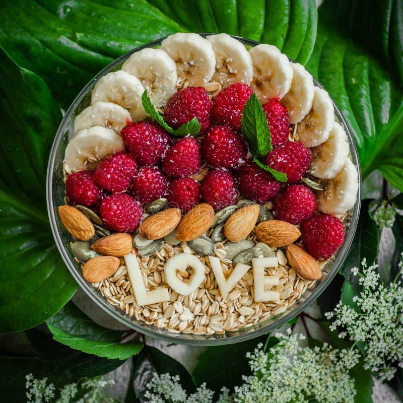 Κατανάλωση του υγιούς κύπελλου προγευμάτων Η ΑΓΑΠΗ λέξης σε ένα πιάτο με ένα υγιές γεύμα Σμέουρο, μπανάνα, καρύδια Χορτοφάγος ένν στοκ εικόνα με δικαίωμα ελεύθερης χρήσης