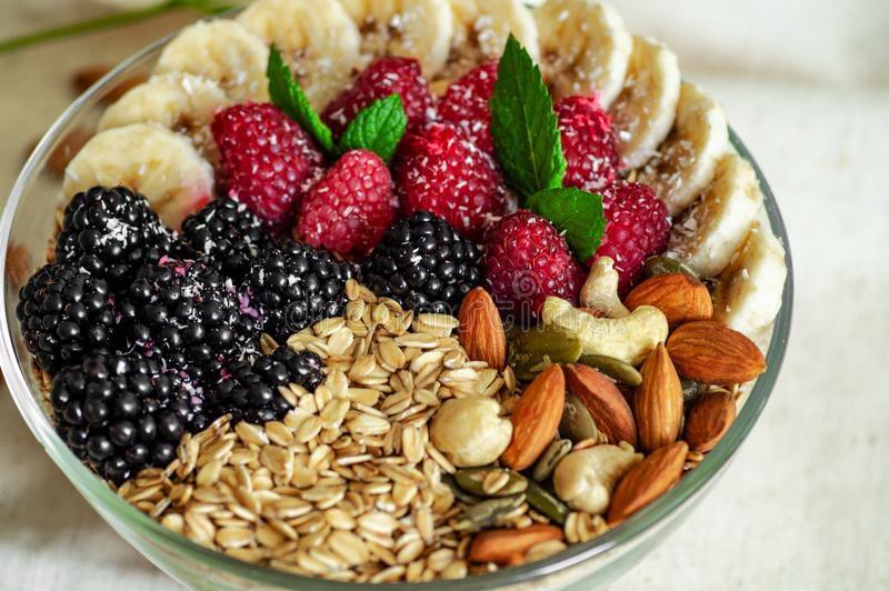 Κατανάλωση του υγιούς κύπελλου προγευμάτων Φρούτα σε ένα πιάτο με ένα υγιές γεύμα Σμέουρο, μπανάνα, καρύδια κάνοντας δίαιτα, χορτ στοκ φωτογραφίες