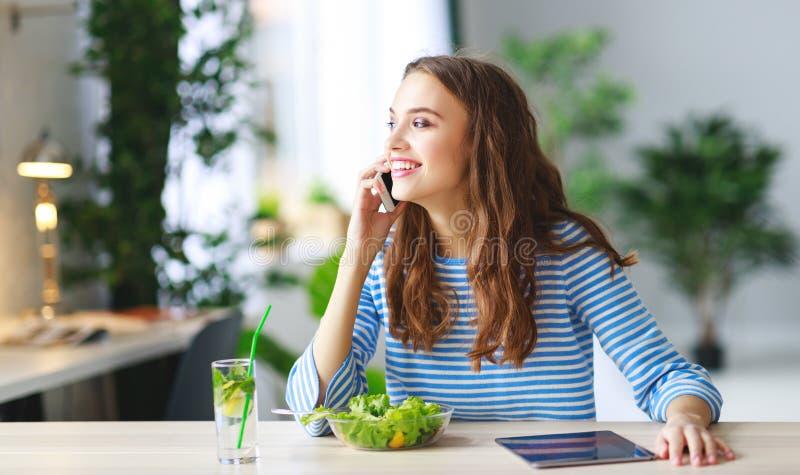 κατανάλωση υγιής ευτυχές νέο κορίτσι που τρώει τη σαλάτα με το PC ταμπλετών το πρωί στην κουζίνα στοκ φωτογραφίες