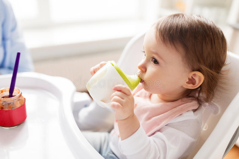 Κατανάλωση μωρών από το φλυτζάνι σωλήνων στο highchair στο σπίτι στοκ εικόνες με δικαίωμα ελεύθερης χρήσης