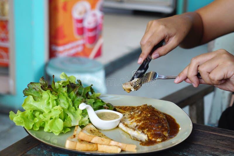 Κατανάλωση που ψήνεται στη σχάρα seabrass με τη μαύρη σάλτσα πιπεριών στοκ φωτογραφίες με δικαίωμα ελεύθερης χρήσης
