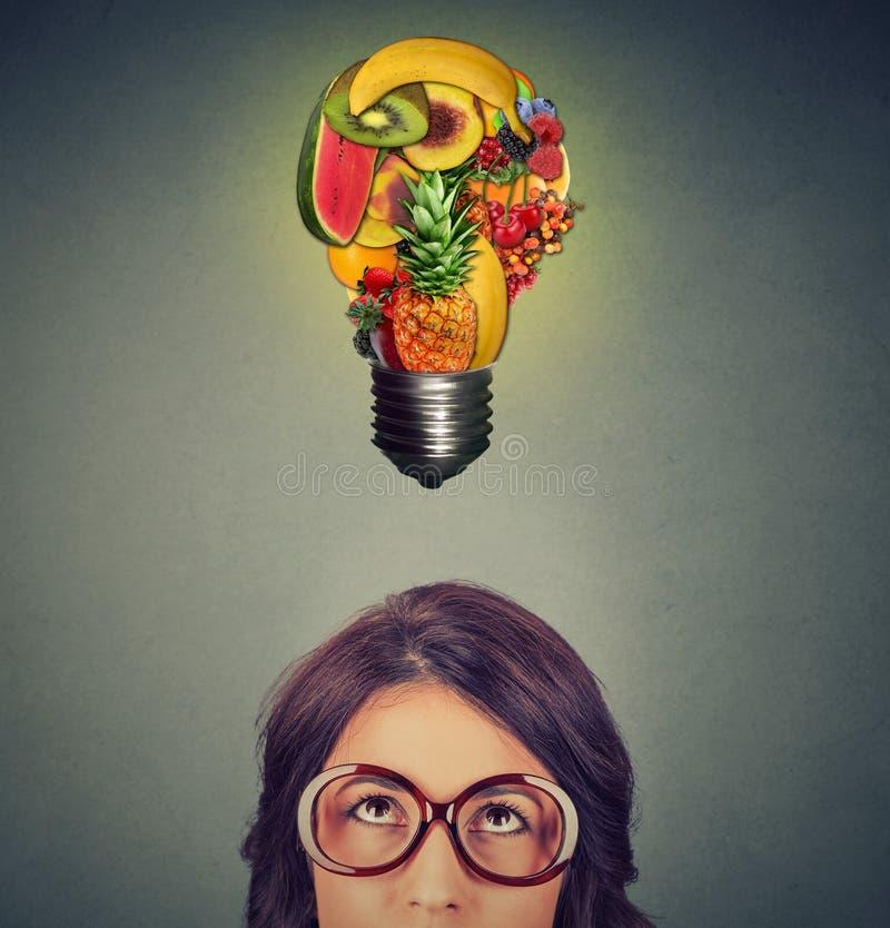Κατανάλωση της υγιούς έννοιας ιδέας γυναίκα που κοιτάζει επάνω στη λάμπα φωτός φιαγμένη από φρούτα επάνω από το κεφάλι στοκ εικόνα με δικαίωμα ελεύθερης χρήσης
