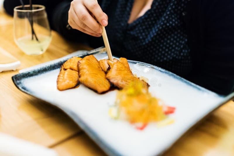 Κατανάλωση του σολομού teriyaki στο εστιατόριο στοκ εικόνες
