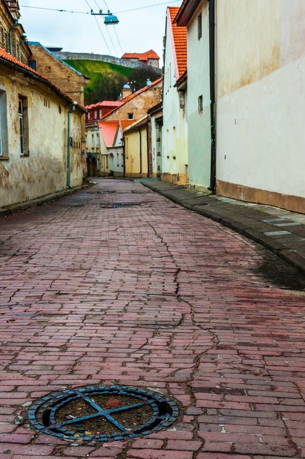Καταπακτή σιδήρου που βρίσκεται στη βρώμικη αλλά μοντέρνη και άνετη παλαιά πόλης οδό σε Vilnius Κλασσικό ευρωπαϊκό σχέδιο οδών αρ στοκ φωτογραφία