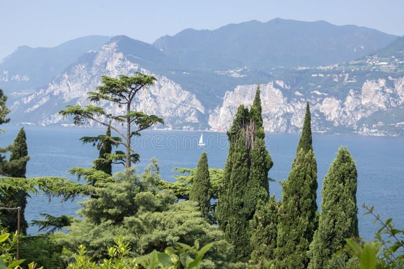 Καταπληκτική άποψη στη λίμνη Lago Di Garda, φως πρωινού, βουνά στο υπόβαθρο, μικρό άσπρο γιοτ στοκ εικόνες