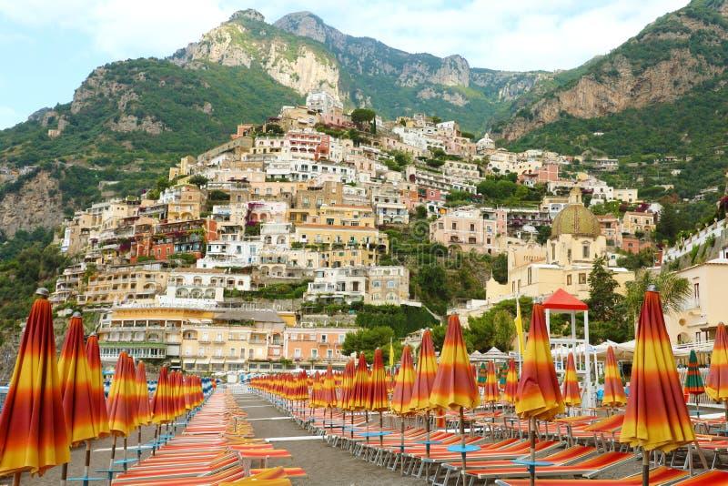Καταπληκτική άποψη της πόλης Positano από την παραλία με τις ομπρέλες και τις καρέκλες γεφυρών, ακτή της Αμάλφης, Ιταλία στοκ εικόνες