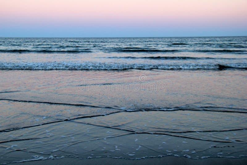 Καταπληκτική ανατολή με τα ευγενή κύματα που περιτυλίγουν την ακτή, pinks και purples που χαιρετούν το πρωί στοκ φωτογραφία με δικαίωμα ελεύθερης χρήσης