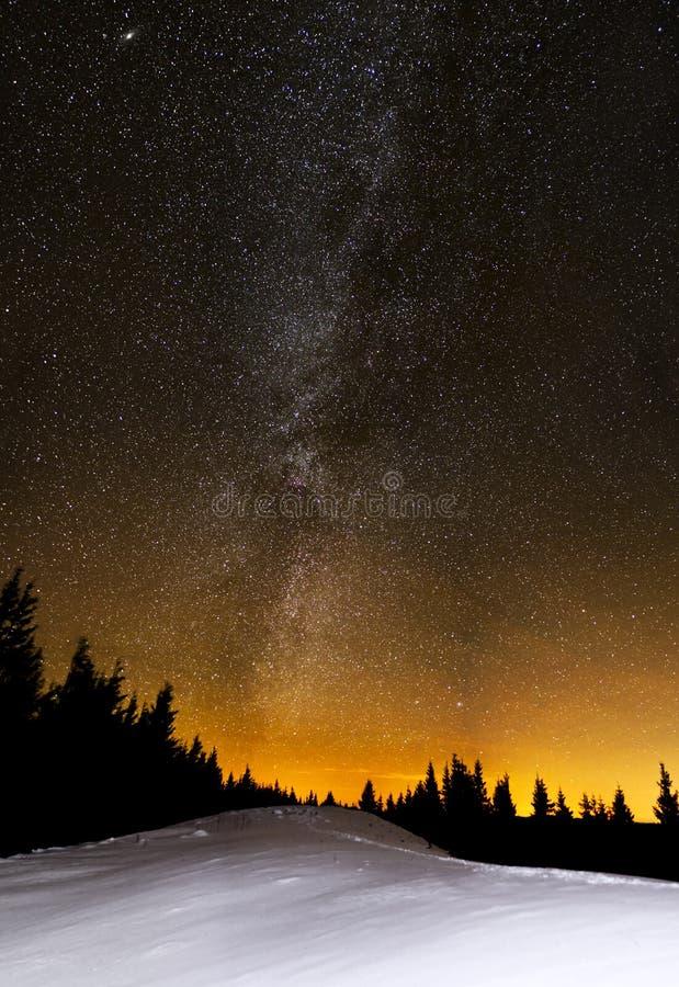 Καταπληκτική νύχτα αστεριών πέρα από τα χιονώδη δέντρα λόφων και έλατου στοκ εικόνα με δικαίωμα ελεύθερης χρήσης