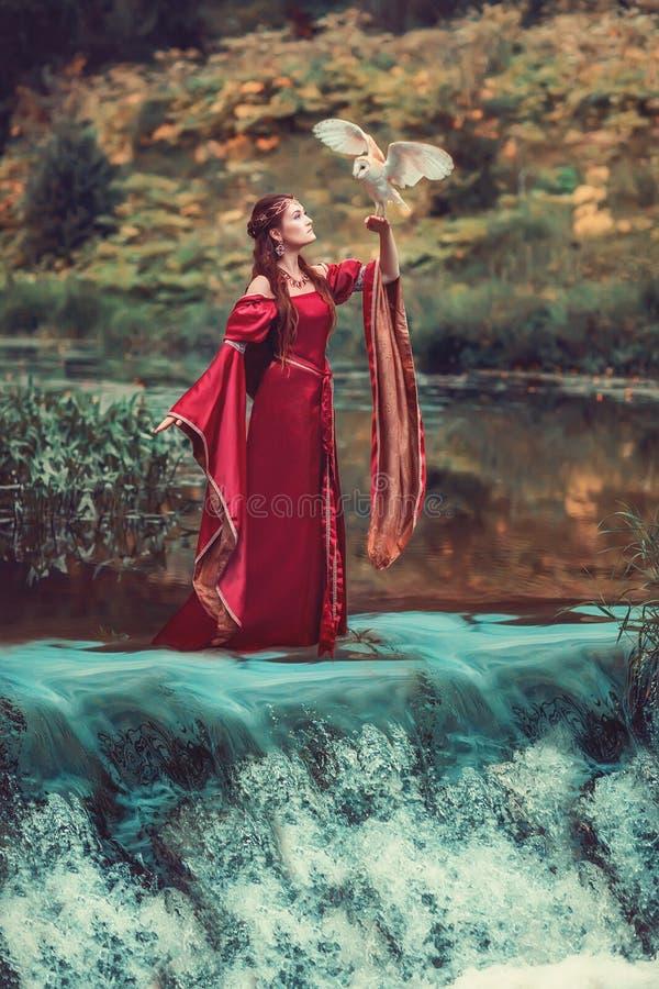 Καταπληκτική σκηνή με τη μεσαιωνική γυναίκα και την πετώντας κουκουβάγια κοντά στον καταρράκτη στοκ φωτογραφία με δικαίωμα ελεύθερης χρήσης