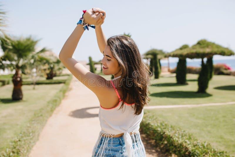 Καταπληκτικός το χαριτωμένο κορίτσι με την καφετιά λαμπρή τρίχα που θέτει πρόθυμα με τα χέρια επάνω στο υπόβαθρο θαμπάδων Λεπτή χ στοκ φωτογραφία με δικαίωμα ελεύθερης χρήσης