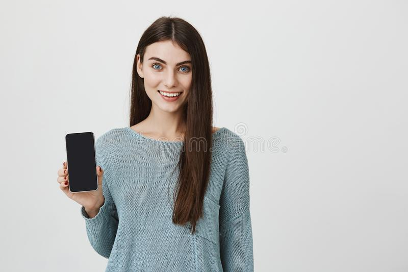 Καταπληκτικό και χαριτωμένο ευρωπαϊκό smartphone εκμετάλλευσης γυναικών σε δεξή χαμογελώντας, που κάνει τη διαφήμιση πέρα από γκρ στοκ εικόνες
