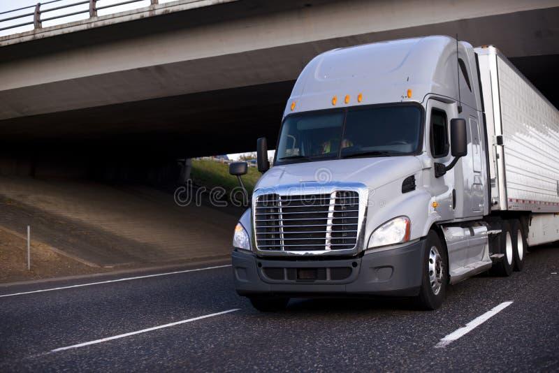 Καταπληκτικό μεγάλο γκρίζο ημι φορτηγό εγκαταστάσεων γεώτρησης με το ημι ρυμουλκό που οδηγεί κάτω στοκ εικόνες