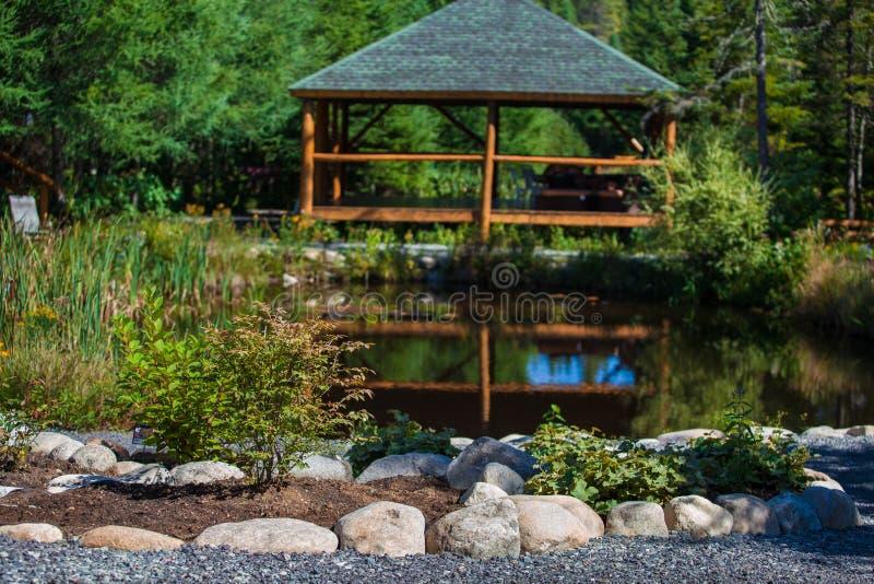 Καταπληκτικό πρόγραμμα εξωραϊσμού με τη λίμνη, τους βράχους, τις εγκαταστάσεις, τα λουλούδια και το ξύλινο gazebo στοκ εικόνες