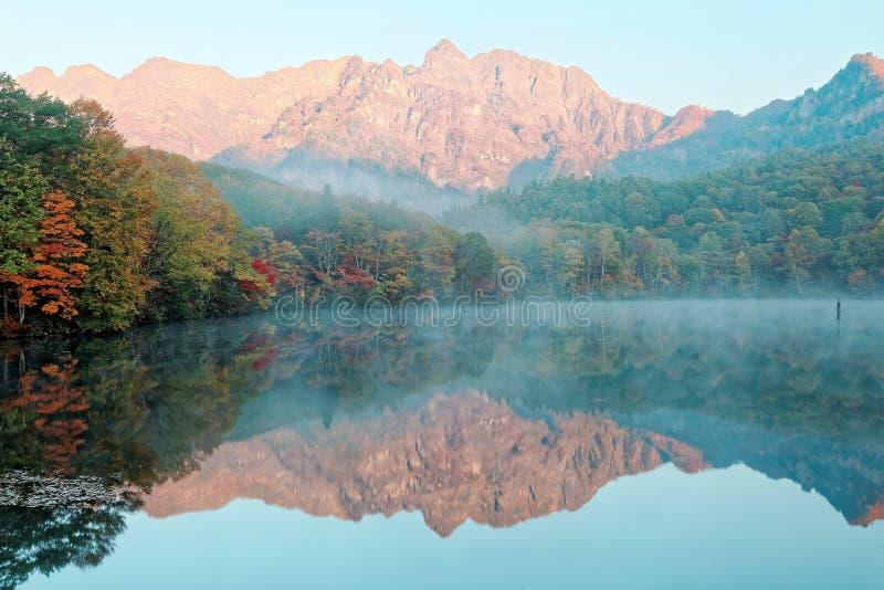Καταπληκτικό τοπίο λιμνών φθινοπώρου της λίμνης καθρεφτών Kagami Ike στο φως πρωινού με τις συμμετρικές αντανακλάσεις του ζωηρόχρ στοκ φωτογραφία