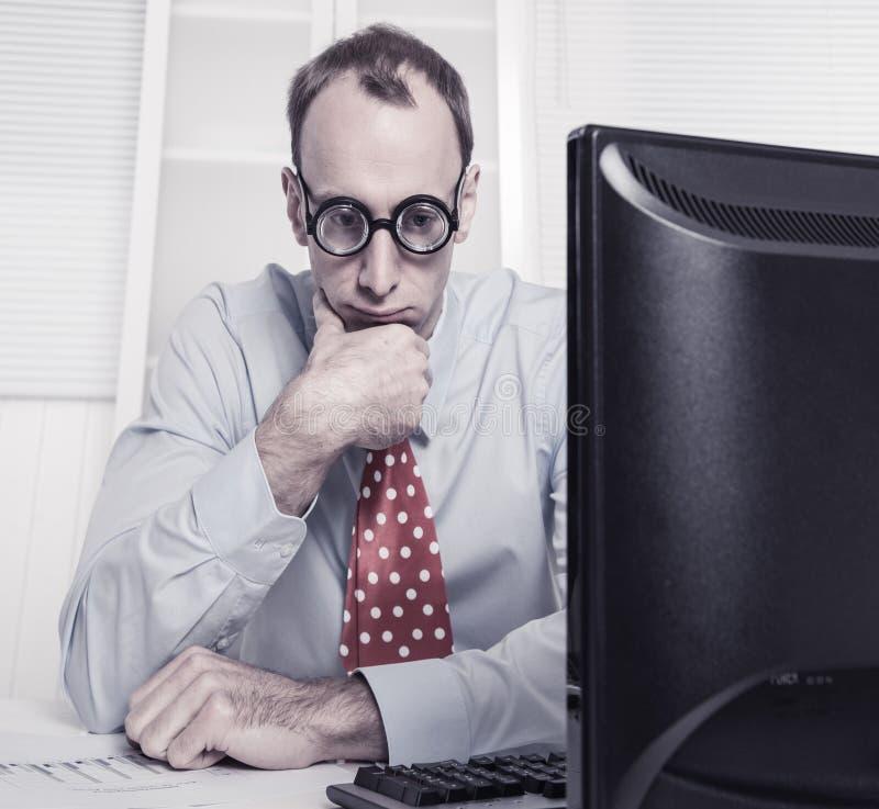 Καταπονημένος επιχειρηματίας με τα γυαλιά που κοιτάζει επίμονα στο διάστημα στο γραφείο στοκ φωτογραφία