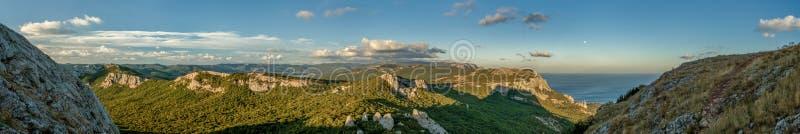 Καταπληκτική ευρεία πανοραμική θέα βουνού με το συμπαθητικό ουρανό και τη θάλασσα στο θερμό φως ήλιων το απόγευμα στοκ φωτογραφίες