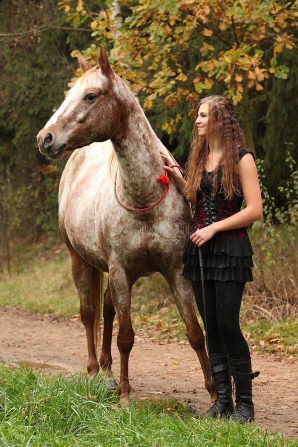 Καταπληκτικό κορίτσι που στέκεται δίπλα στο άλογο appaloosa στοκ εικόνα