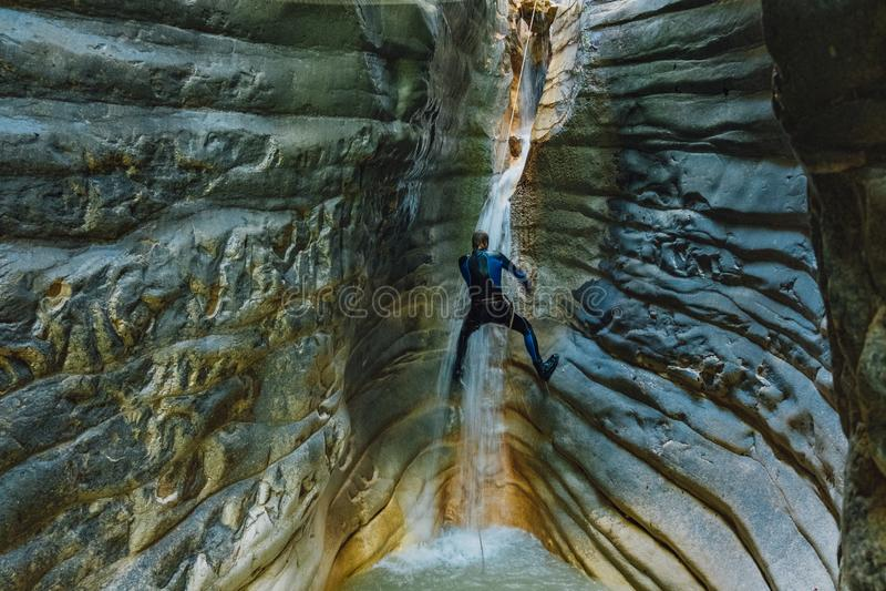 Καταρράκτης Rappelling Το άτομο στο υγρό κοστούμι αναρριχείται στον καταρράκτη στο στενό φαράγγι ποταμών στοκ φωτογραφίες