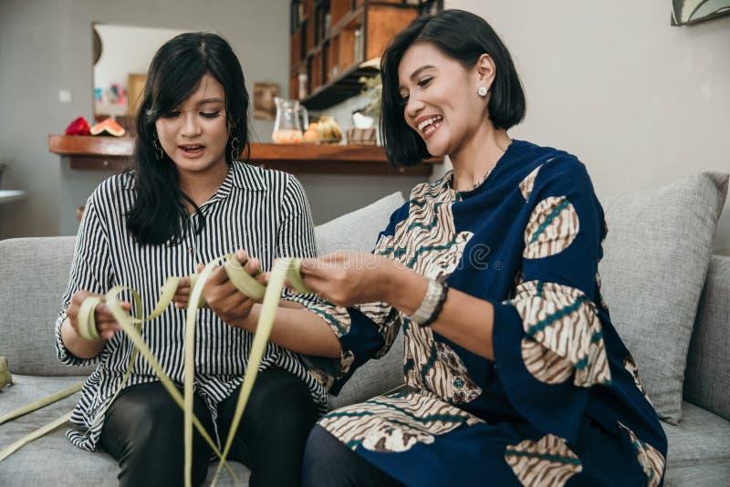 Κατασκευάζοντας ketupat τα παραδοσιακά ινδονησιακά τρόφιμα από κοινού στοκ εικόνα