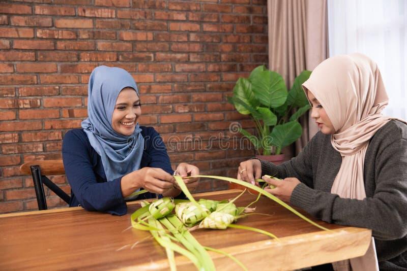 Κατασκευάζοντας ketupat τα παραδοσιακά ινδονησιακά τρόφιμα από κοινού στοκ εικόνες