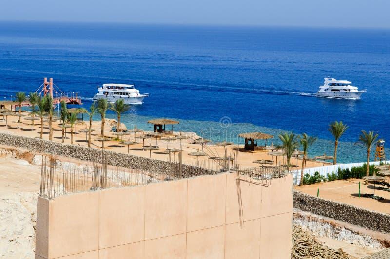 Κατασκευή ενός ξενοδοχείου στην έρημο σε ένα θερμό τροπικό νότιο εξωτικό θέρετρο διακοπών ενάντια σε μια μπλε θάλασσα των φοινίκω στοκ φωτογραφία με δικαίωμα ελεύθερης χρήσης