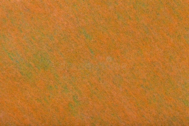 Κατασκευή ενός φωτεινού πορτοκαλιού υποβάθρου με τα ανοικτό πράσινο σημεία του αισθητού υφάσματος, κινηματογράφηση σε πρώτο πλάνο στοκ εικόνα με δικαίωμα ελεύθερης χρήσης