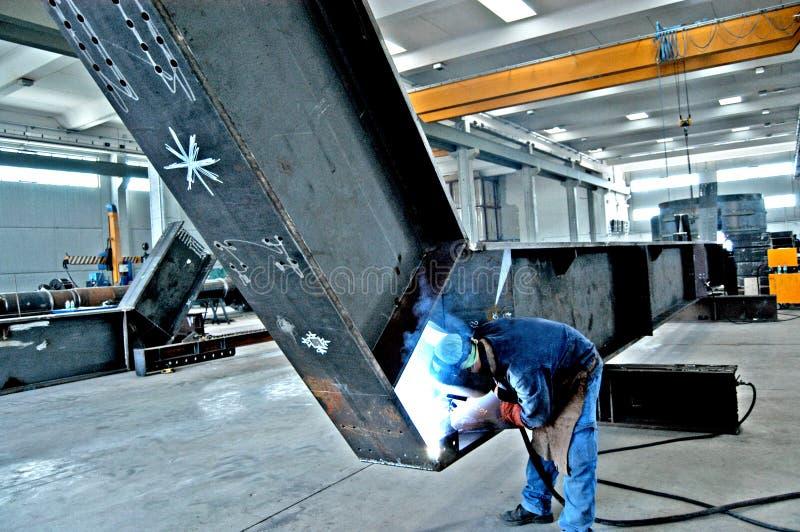 Κατασκευή σιδηρουργείου των μεγάλων σωλήνων με τους εργαζομένους που απασχολούνται στη μηχανή συγκόλλησης στοκ εικόνα με δικαίωμα ελεύθερης χρήσης